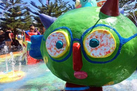 A sculpture of a green-faced man with blue glasses and a red nose spouts water from spiky hair atVera's Water Garden.
