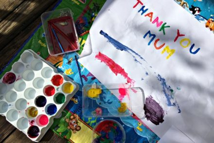 "Child's painting saying, ""Thank you Mum"" in bright paint colours"